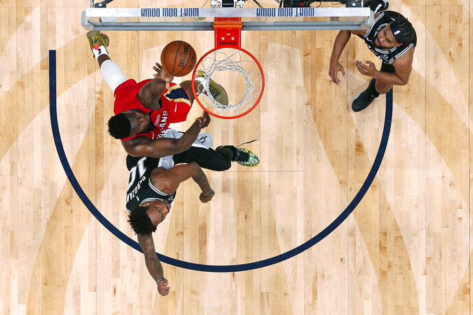 New Orleans Pelicans forward Zion Williamson goes to the basket against San Antonio Spurs forward DeMar DeRozan (10) in the second half of an NBA basketball game in New Orleans, Wednesday, Jan. 22, 2020. The Spurs won 121-117. (AP Photo/Gerald Herbert)