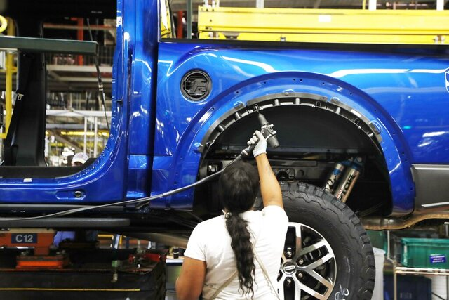 FILE - In this Sept. 27, 2018, file photo a United Auto Workers assemblyman works on a 2018 Ford F-150 truck being assembled at the Ford Rouge assembly plant, in Dearborn, Mich. Ford Motor Co. said Tuesday, Dec. 17, 2019, that it is adding 3,000 jobs at two factories in the Detroit area and investing $1.45 billion to build new pickup trucks, SUVs, and electric and autonomous vehicles. At the Dearborn truck plant $700 million will be invested. (AP Photo/Carlos Osorio, File)