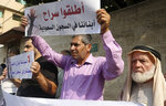 Families of Palestinians held in jails in Saudi Arabia, hold placards in Arabic that read,