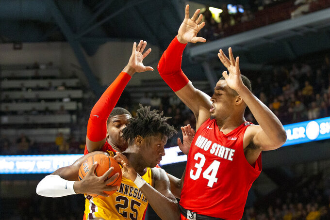 Minnesota center Daniel Oturu (25) looks for an opening against Ohio State center Kaleb Wesson (34) and guard D.J. Carton in the first half of an NCAA college basketball game Sunday, Dec. 15, 2019 in Minneapolis. (AP Photo/Andy Clayton-King)