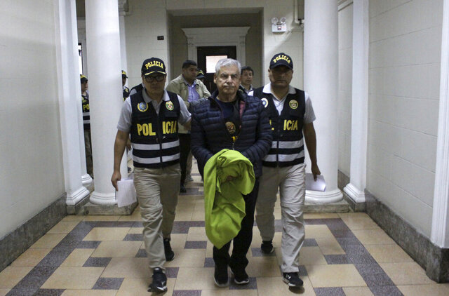 In this handout photo provided by Peru's Palace of Justice Press Office, former Prime Minister Cesar Villanueva is escorted by police to a courtroom, at the Palace of Justice in Lima, Peru, Wednesday, Nov. 27, 2019. Villanueva was placed under preventive detention while being investigated for influence peddling in a bribery case linked to the Brazilian construction company Odebrecht, the Public Ministry said Wednesday. (Francisco Medina/Peru's Palace of Justice press office via AP)