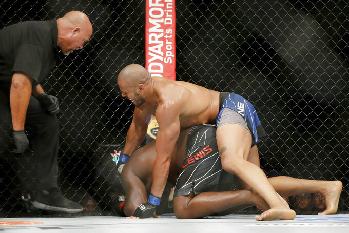 Derrick Lewis, bottom, is pummeled against the fence by Ciryl Gane, resulting in a technical knockout called by referee Dan Miragliotta, left, in the third round of their interim heavyweight mixed martial arts title bout at UFC 265 on Saturday, Aug. 7, 2021, in Houston. (AP Photo/Michael Wyke)