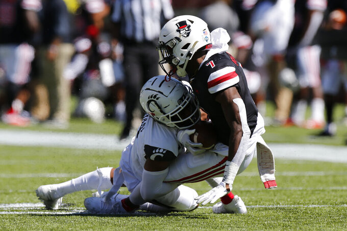 Cincinnati defensive back Coby Bryant, left, tackles Austin Peay wide receiver Geordon Pollard during the first half of an NCAA college football game Saturday, Sept. 19, 2020, in Cincinnati, Ohio. (AP Photo/Jay LaPrete)