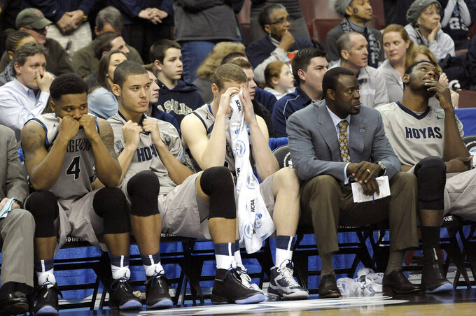 FILE - In this March 22, 2013, file photo, Georgetown players and personnel react on the bench in the final minutes of a second-round game against Florida Gulf Coast in the NCAA college basketball tournament in Philadelphia. Florida Gulf Coast won 78-68. The high-flying FGSU Eagles and their showstopping offense earned their place in NCAA Tournament lore when, as a No. 15 seed in the South Region, they upset Georgetown and San Diego State in Philadelphia to reach the 2013 Sweet 16. (AP Photo/Michael Perez, File)