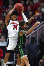 South Carolina Upstate guard Thomas Booker, right, attempts to steal the ball from Louisville forward Dwayne Sutton, left, during the first half of an NCAA college basketball game in Louisville, Ky., Wednesday, Nov. 20, 2019. (AP Photo/Timothy D. Easley)