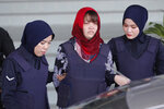 Vietnamese Doan Thi Huong, center, is escorted by police as she leaves Shah Alam High Court in Shah Alam, Malaysia, Thursday, March 14, 2019. Malaysia's attorney general ordered the murder case to proceed against the Vietnamese woman accused in the killing of the North Korean leader's estranged half brother, prosecutors said in court Thursday.(AP Photo/Vincent Thian)