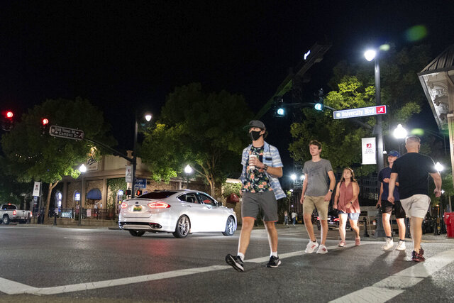 People make their way along The Strip, the University of Alabama's bar scene, Saturday, Aug. 15, 2020, in Tuscaloosa, Ala. More than 20,000 students returned to campus for the first time since spring break, with numerous school and city codes in effect to limit the spread of COVID-19. (AP Photo/Vasha Hunt)