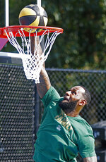 LeBron James dunks during the debut of the new basketball court at I Promise School, Wednesday, Aug. 14, 2019 in Akron, Ohio. (Jeff Lange/Akron Beacon Journal via AP)