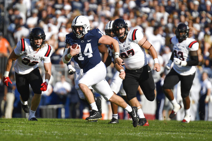 Penn State quarterback Sean Clifford (14) breaks away from the Ball State defense on a long gain during the first half of an NCAA college football game in State College, Pa., Saturday, Sept. 11, 2021. (AP Photo/Barry Reeger)