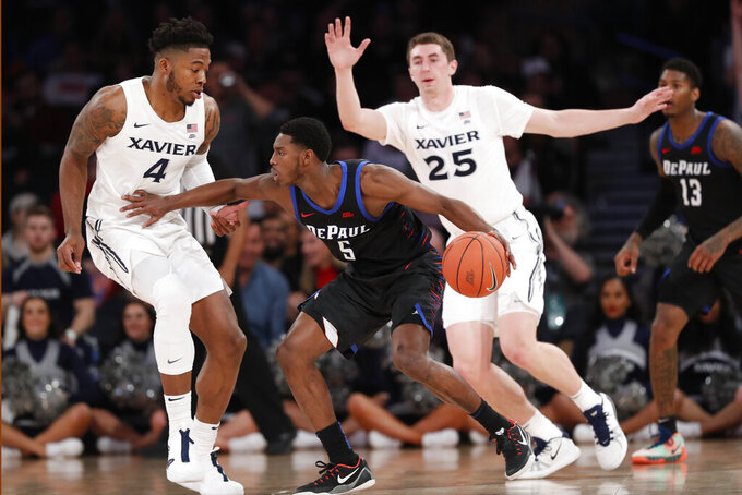 DePaul guard Jalen Coleman-Lands (5) fends off Xavier forwards Tyrique Jones (4) and Jason Carter (25) during the first half of an NCAA college basketball game in the first round of the Big East men's tournament Wednesday, March 11, 2020, in New York. (AP Photo/Kathy Willens)