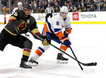 Vegas Golden Knights right wing Reilly Smith (19) shoots as New York Islanders defenseman Noah Dobson (8) defends during the second period of an NHL hockey game Saturday, Feb. 15, 2020, in Las Vegas. (AP Photo/Isaac Brekken)