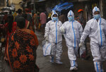 Health workers return after screening people for COVID-19 symptoms in Dharavi, one of Asia's biggest slums, in Mumbai, India, Tuesday, Aug. 11, 2020. India has the third-highest coronavirus caseload in the world after the United States and Brazil. (AP Photo/Rafiq Maqbool)