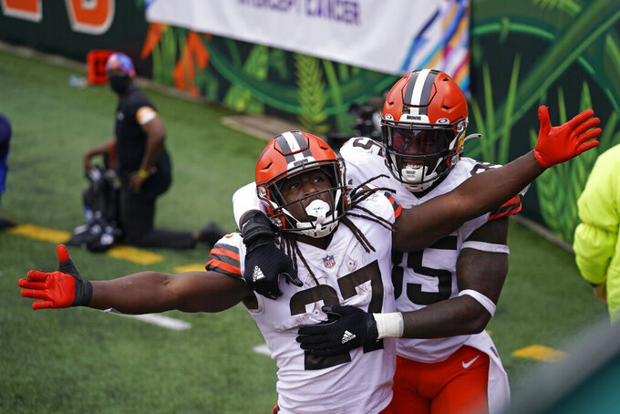 Cleveland Browns' Kareem Hunt (27) celebrates his touchdown with David Njoku (85) during the second half of an NFL football game against the Cincinnati Bengals, Sunday, Oct. 25, 2020, in Cincinnati. (AP Photo/Bryan Woolston)
