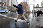 A man leaps to cross the street flooded by a water main break, in New York, Monday, Jan. 13, 2020. A water main break flooded streets on Manhattan's Upper West Side near Lincoln Center and hampered subway service during the Monday morning rush hour. (AP Photo/Richard Drew)
