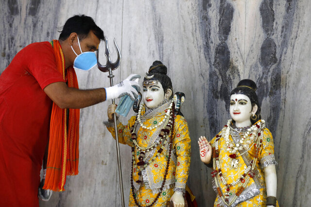 An Indian priest sanitizes the idol of Lord Shiva and Godess Parvati at a temple, in Prayagraj, India, Monday, June 8, 2020. Religious places, malls, hotels and restaurants open Monday after more than two months of lockdown as a precaution against coronavirus. (AP Photo/Rajesh Kumar Singh)