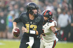 Purdue quarterback Jack Plummer (13) is chase out of the pocket by Oregon State linebacker Andrzej Hughes-Murray (2) during the first half of an NCAA college football game in West Lafayette, Ind., Saturday, Sept. 4, 2021. (AP Photo/Michael Conroy)
