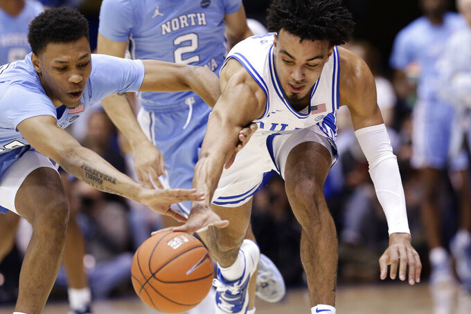 North Carolina guard Christian Keeling, left, and Duke guard Tre Jones chase the ball during the first half of an NCAA college basketball game in Durham, N.C., Saturday, March 7, 2020. (AP Photo/Gerry Broome)