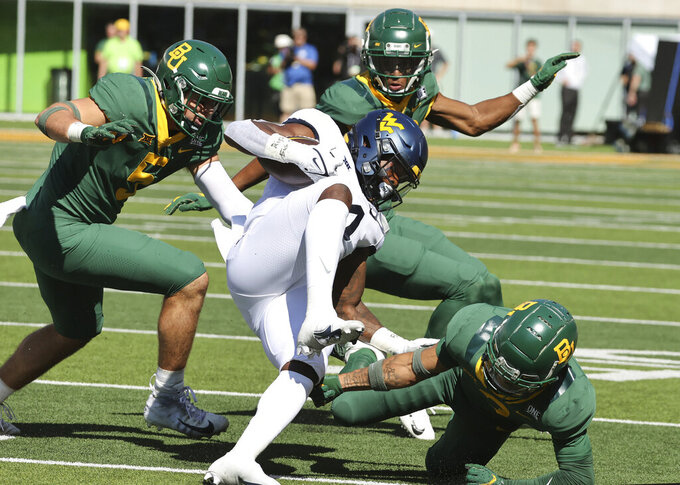 Baylor cornerback Raleigh Texada, right, and Dillon Doyle, left, bring down West Virginia running back Leddie Brown in the first half  of an NCAA college football game, Saturday, Oct. 9, 2021, in Waco, Texas. (Rod Aydelotte/Waco Tribune-Herald via AP)