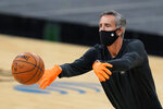 San Antonio Spurs assistant coach Chip Engelland wears a face mask and gloves to protect against the spread of COVID-19 as he helps the team warm up prior to an NBA basketball game against the Los Angeles Lakers in San Antonio, Wednesday, Dec. 30, 2020. (AP Photo/Eric Gay)
