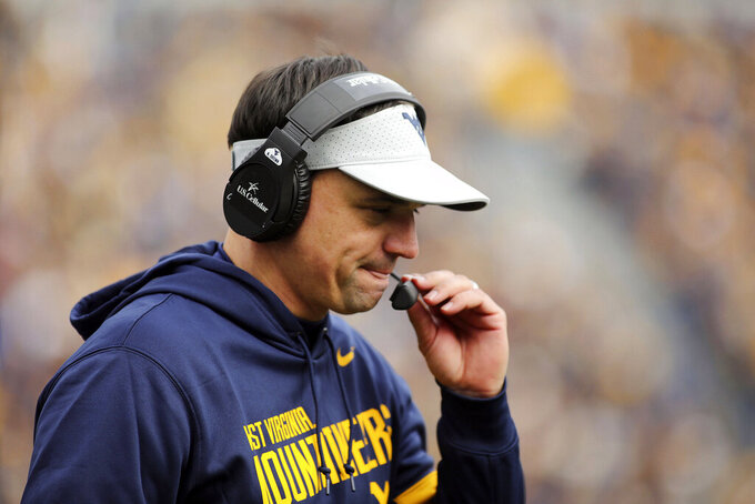 West Virginia head coach Neal Brown holds his mic during their NCAA college football game against Texas Tech in Morgantown, W.Va., Saturday, Nov. 9, 2019. (AP Photo/Chris Jackson)