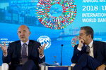 European Commissioner for Economic and Financial Affairs Pierre Moscovici, left, talks as Director General of the World Trade Organization (WTO) Roberto Azevedo listens during a seminar in Bali, Indonesia, Wednesday, Oct. 10, 2018. (AP Photo/Firdia Lisnawati)
