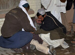 People comfort a man, who lost his family member in mosque bombing, at a hospital in Quetta, Pakistan, Friday, Jan. 10, 2020. A powerful explosion ripped through a mosque in southwest Pakistan during Friday evening prayers, killing a senior police officer with some civilians and wounded other worshipers, police said. (AP Photo/Arshad Butt)