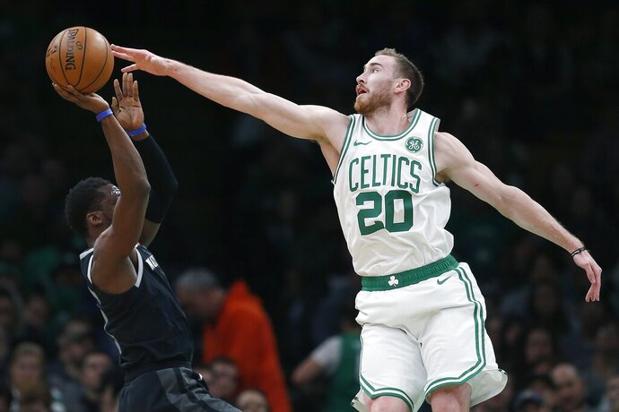 Boston Celtics' Gordon Hayward (20) defends against Detroit Pistons' Reggie Jackson (1) during the first half of an NBA basketball game in Boston, Wednesday, Feb. 13, 2019. (AP Photo/Michael Dwyer)