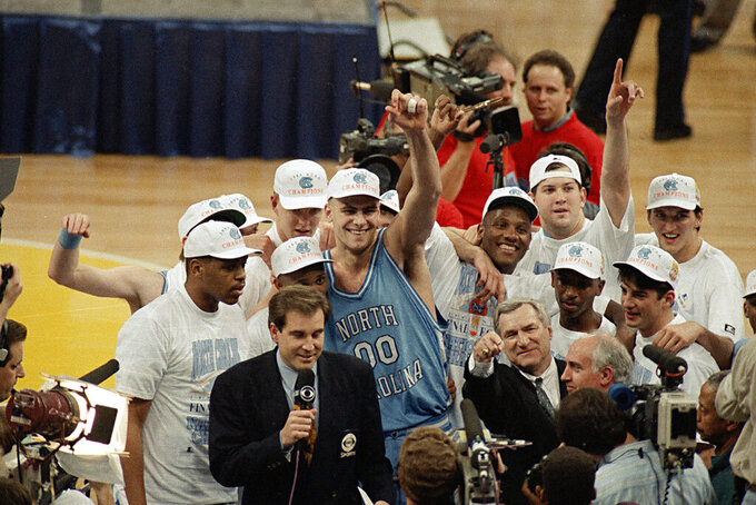 FILE - In this April 5, 1993, file photo, North Carolina coach Dean Smith at front center right, points as he celebrates a 77-71 win against Michigan in the NCAA Final Four championship basketball game in New Orleans. At center is Eric Montross (00). The game wasn't settled until Michigan's Chris Webber called a timeout the Wolverines didn't have with 11 seconds to go. ″You can call it lucky, you can call it fortunate, but it still says NCAA championship,″ Smith said. (AP Photo/Bob Jordan, File)