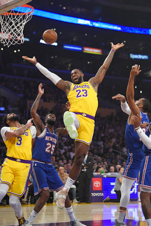 Los Angeles Lakers forward LeBron James (23) has the ball knocked from his hands while trying to shoot by New York Knicks guard Wayne Ellington, right, as forward Anthony Davis, left, and guard Reggie Bullock vie for position during the first half of an NBA basketball game Tuesday, Jan. 7, 2020, in Los Angeles. (AP Photo/Mark J. Terrill)