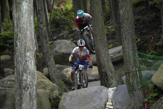 Thomas Pidcock of Great Britain (29) and Nino Schurter of Switzerland (1), behind, competeduring the men's cross country mountain bike competition at the 2020 Summer Olympics, Monday, July 26, 2021, in Izu, Japan. (AP Photo/Christophe Ena)