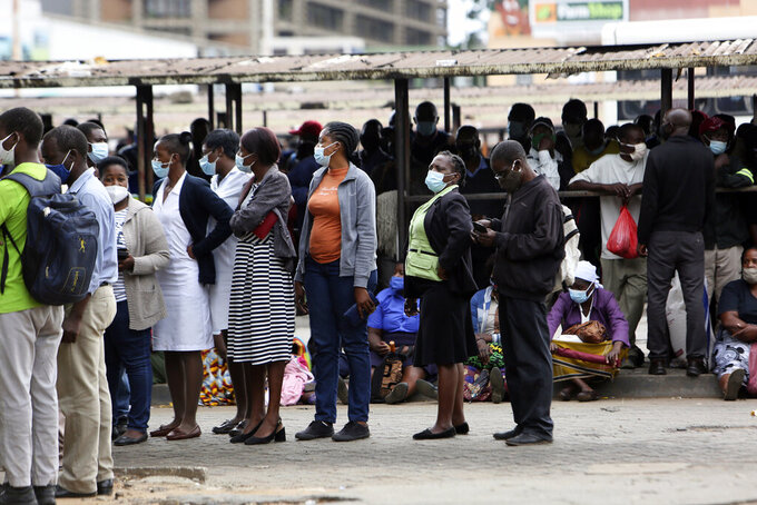 People wait at a bus station in Harare, Zimbabwe, Thursday, Sept, 16, 2021. Zimbabwe has told all government employees to get vaccinated against COVID-19 or they will not be allowed to come to work. It wasn't made clear what would happen to those who refused to be vaccinated. (AP Photo/Tsvnagirayi Mukwazhi)