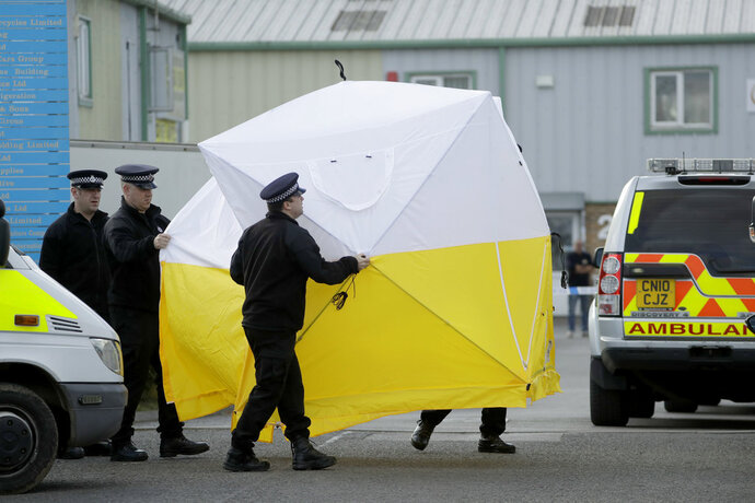 Police officers position a screen outside the vehicle recovery business