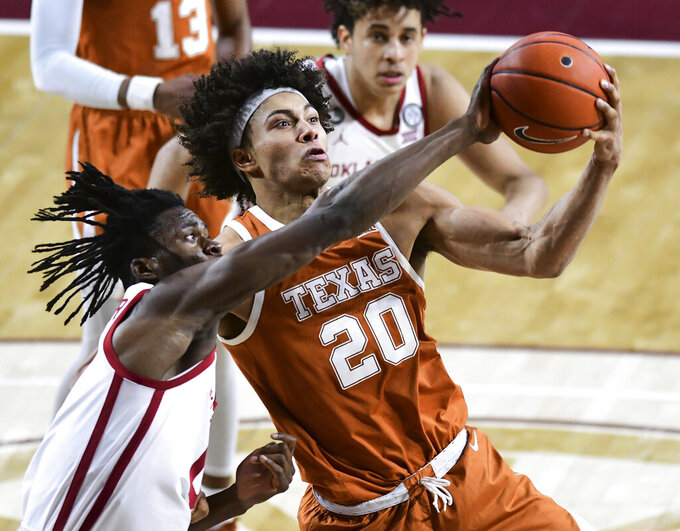Texas forward Jericho Sims (20) grabs a rebound over Oklahoma Victor Iwuakor (0) during the first half of an NCAA college basketball game in Norman, Okla., Thursday, March 4, 2021. (AP Photo/Kyle Phillips)