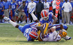 LSU quarterback Joe Burrow (9) is tackled by Florida defensive back Chauncey Gardner-Johnson (23) and defensive back CJ Henderson, right, after running for a first down during the first half of an NCAA college football game, Saturday, Oct. 6, 2018, in Gainesville, Fla. (AP Photo/John Raoux)