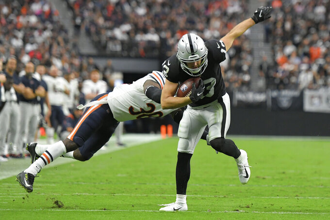 Las Vegas Raiders wide receiver Hunter Renfrow (13) breaks a tackle by Chicago Bears safety Tashaun Gipson (38) during the second half of an NFL football game, Sunday, Oct. 10, 2021, in Las Vegas. (AP Photo/David Becker)