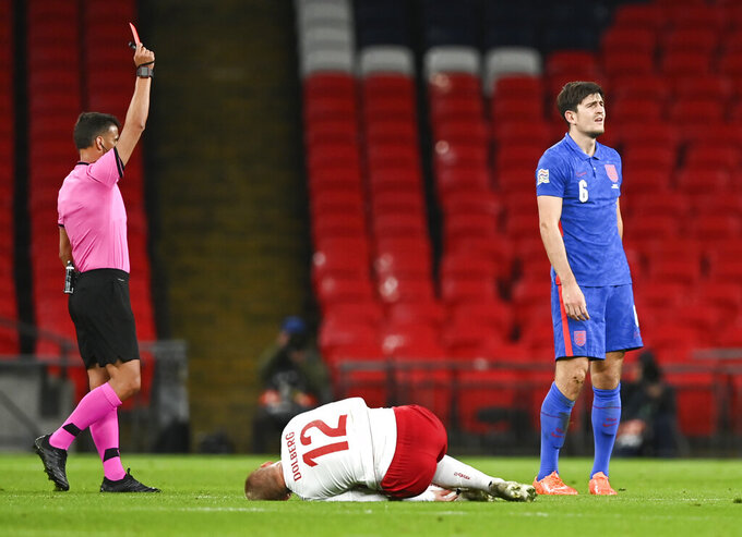 England's Harry Maguire, right, reacts as he is shown a red card by referee Jesus Gil Manzano, left, during the UEFA Nations League soccer match between England and Denmark at Wembley Stadium in London, England, Wednesday, Oct. 14, 2020. (Daniel Leal-Olivas/Pool via AP)