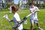 Owen Estee, Acalanes High School Varsity Lacrosse player, coaches 9-year-old Bobby Ruhl on Tuesday, July 28, 2020 in Orinda, Calif. Owen and his friend Zach Appel have launched Lacrosse Against Hunger, to offer lacrosse coaching sessions to 7-14 year olds in exchange for a charitable donation to White Pony Express. All money raised goes directly to White Pony Express through Lacrosse Against Hunger's GoFundMe page. (AP Photo/Tony Avelar)