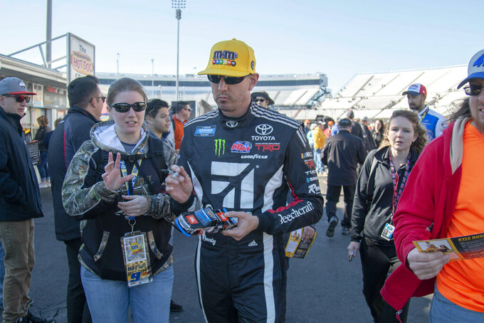 Kyle Bush signs autographs after qualifying second for the NASCAR Gander Outdoors Truck Series race at Martinsville Speedway in Martinsville, Va. Saturday, March 23. (AP Photo/Matt Bell)