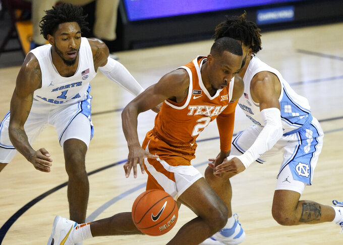 Texas guard Matt Coleman III (2) drives between North Carolina guards Leaky Black (1) and R.J. Davis (4) during the first half of an NCAA college basketball game for the championship of the Maui Invitational, Wednesday, Dec. 2, 2020, in Asheville, N.C. (AP Photo/Kathy Kmonicek)