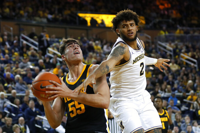 Michigan forward Isaiah Livers (2) fouls Iowa center Luka Garza (55) in the second half of an NCAA college basketball game in Ann Arbor, Mich., Friday, Dec. 6, 2019. (AP Photo/Paul Sancya)