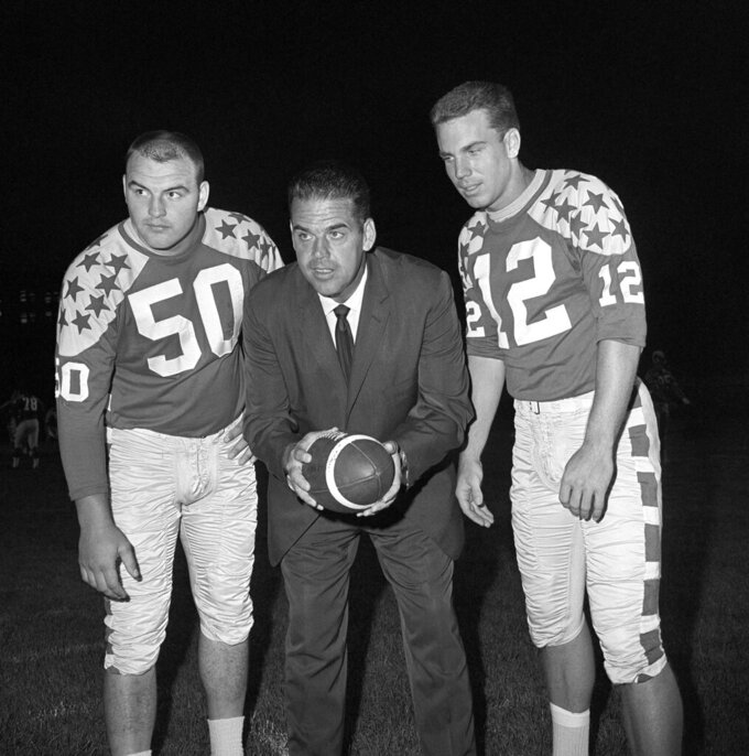 FILE - In this Aug. 5, 1965, file photo, Otto Graham, center, coach of the College All Stars football team, talks with co-captains Dick Butkus (50) of Illinois and Roger Staubach (12) of Navy as the team worked out under lights at Soldier Field in Chicago. In the early days of the NFL, college football was king and playing the game professionally was not necessarily something players aspired to do. By planting its flag in large cities, embracing television exposure and playing a more entertaining style, the NFL surged in popularity in the middle of the 20th century and helped turn college football into a means to an end for many players. (AP Photo/Edward Kitch, File)