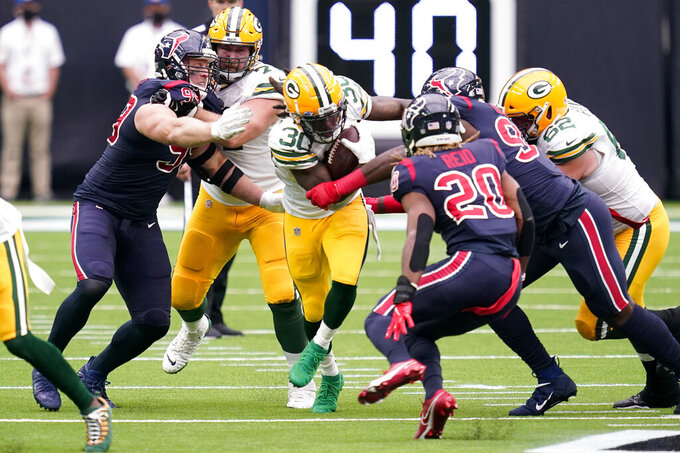 Green Bay Packers running back Jamaal Williams (30) runs with the ball as Houston Texans defensive end J.J. Watt, left, and safety Justin Reid (20) defend during the first half of an NFL football game Sunday, Oct. 25, 2020, in Houston. (AP Photo/Sam Craft)