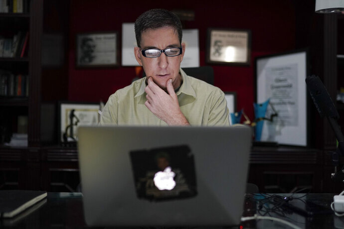 In this July 10, 2019 photo, U.S. journalist Glenn Greenwald checks his news website at his home in Rio de Janeiro, Brazil. Greenwald, an attorney-turned-journalist who has long been a free-speech advocate, has found himself at the center of the first major test of press freedom under Brazil's President Jair Bolsonaro, who took office on Jan. 1 and has openly expressed nostalgia for Brazil's 1964-1985 military dictatorship, a period when newspapers were censored and some journalists tortured. (AP Photo/Leo Correa)