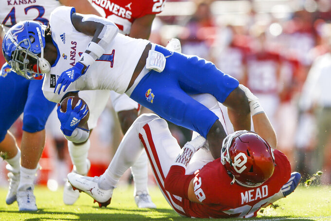 Oklahoma's Bryan Mead (38) tackles Kansas' Kenny Logan Jr. (1) on a kick return during an NCAA college football game in Norman, Okla., Saturday, Nov. 7, 2020. (Ian Maule/Tulsa World via AP)