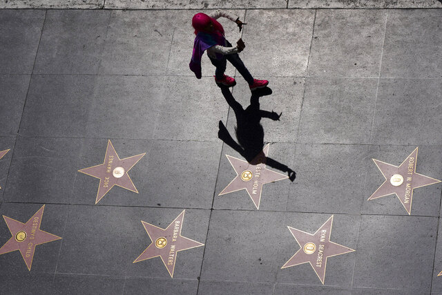 In this photo taken Wednesday, March 18, 2020, a person takes a selfie as she walks along the Walk of Fame on Hollywood Boulevard in the Hollywood section of Los Angeles. The coronavirus is hitting California's most famous tourist sites hard. From Disneyland to Yosemite National Park, the Golden State's iconic destinations are closed or shuttering amenities to prevent the spread of the pandemic. (AP Photo/Mark J. Terrill)