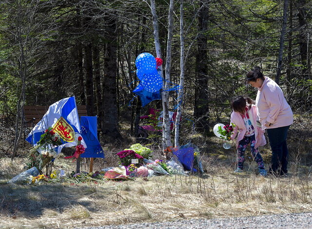 A memorial pays tribute to Heather O'Brien, a victim of this past weekend shootings along the highway in Debert, Nova Scotia, on Tuesday, April 21, 2020. RCMP say several people are dead after a man who at one point wore a police uniform and drove a mock-up cruiser, went a murder rampage in Portapique, and other Nova Scotia communities. The alleged killer was shot and killed by police. (Andrew Vaughan/The Canadian Press via AP)