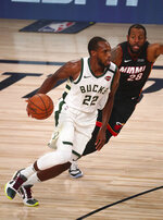 August 6, 2020; Lake Buena Vista, Florida, USA; Milwaukee Bucks forward Khris Middleton (22) moves the ball against Miami Heat guard Andre Iguodala (28) during the second half of an NBA basketball game Thursday, Aug. 6, 2020, in Lake Buena Vista, Fla. (Kim Klement/Pool Photo via AP)