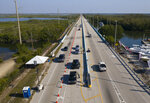 This aerial photo provided by the Florida Keys News Bureau, shows a checkpoint at the top of the Florida Keys Overseas Highway, Friday, March 27, 2020, near Key Largo, Fla. The Keys have been temporarily closed to visitors and non-residents since March 22, because of the coronavirus crisis. (Andy Newman/Florida Keys News Bureau via AP)