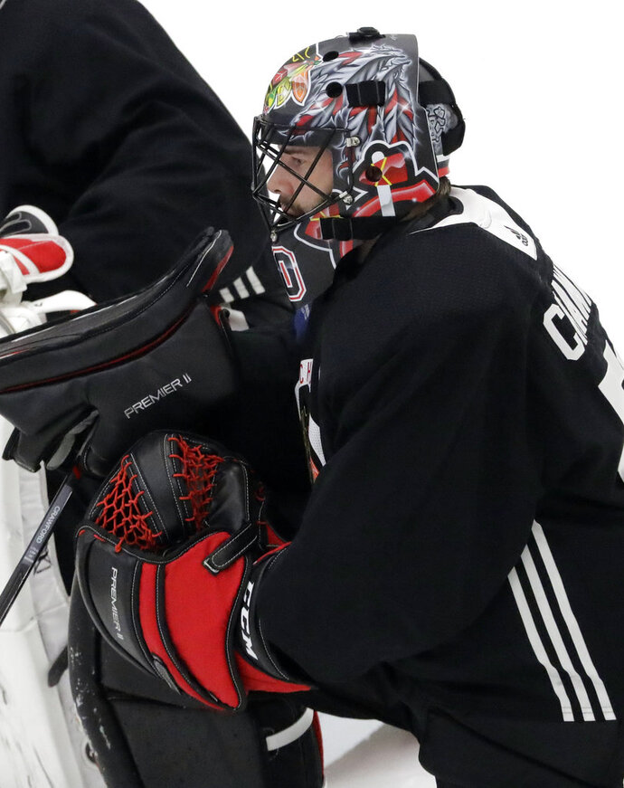 Chicago Blackhawks goalie Corey Crawford listens to a coach during NHL hockey training camp at the MB Ice Arena, Friday, Sept. 14, 2018, in Chicago. (AP Photo/Nam Y. Huh)