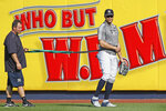 New York Yankees' Giancarlo Stanton, right, who has been out the much of the season with various injuries, takes a break as he works with a trainer and a resistance band in the outfield before a baseball game between the Yankees and the Texas Rangers, Wednesday, Sept. 4, 2019, in New York. (AP Photo/Kathy Willens)